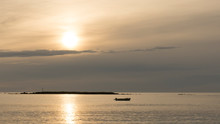 A Fishing Boat Anchored In A Bay At Sunrise Or Sunset In Backlight With Cloudy Sky