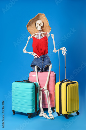 Human skeleton in summer clothes with suitcases on blue background Wallpaper Mural