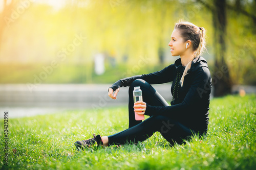 Fototapeta young pretty thirsty blonde Caucasian girl in suit resting after sport run in the football stadium sitting on grass drinking water and smiling enjoying and listening music with her wireless headphones obraz