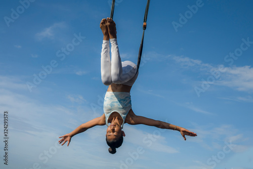 Photo outdoors portrait of young happy and athletic Asian Indonesian woman doing aero