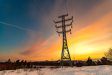 High Voltage Electricity Pylons And Transmission Power Lines On The Blue Sky Background At Sunset.