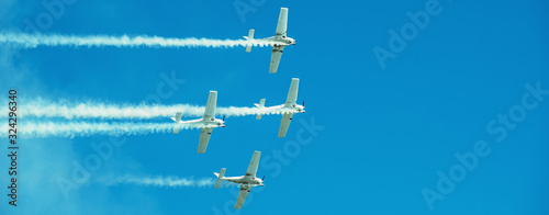 Vászonkép Panorama of Airplanes with white smoke traces on air show, copy space