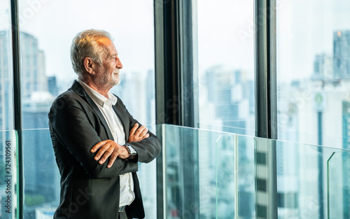 Fototapeta Retirement Man Concept.Portrait of Senior grey-haired businessman in suit standing and and looking through window the cityscape. obraz