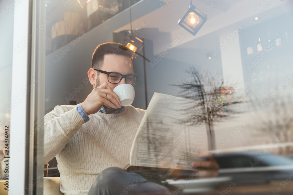 Fototapeta Man reading newspapers and drinking coffee