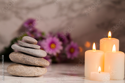 river pebbles and four lighted candles with daisies unfocused