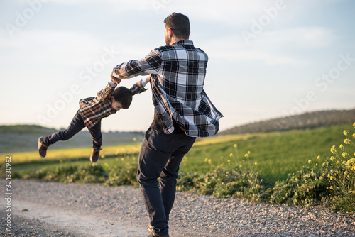 Obraz Spinning father grabbing his son with his arms - fototapety do salonu
