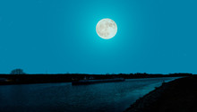 A Cargo Ship At Night On The Mittelland Canal In Germany Near The Magdeburg Water Cross. It Is A Romantic Full Moon Night. You Can See The Position Lights On The Ship And Reflections In The Water.