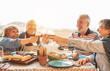 canvas print picture - Happy senior dining and tasting red wine glasses in barbecue dinner party - Family having fun enjoying bbq at sunset time on terrace - Elderly people lifestyle and food and drink concept