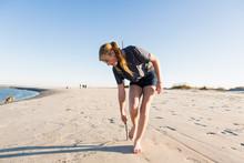 Teenage Girl Playing In Sand O...