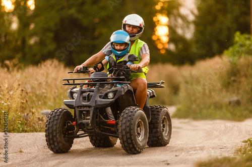 Fototapeta little boy with instructor on a quad bike obraz