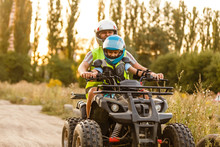 Little Boy With Instructor On A Quad Bike