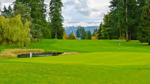 Golf Course With Gorgeous Green, Golf Flag And Pond.