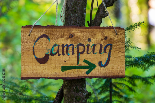 Fotografia A soft focus closeup view of a handcrafted wood directional campsite sign, woodl
