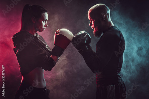 Woman exercising with trainer at boxing and self defense lesson, studio, smoke on background Tapéta, Fotótapéta
