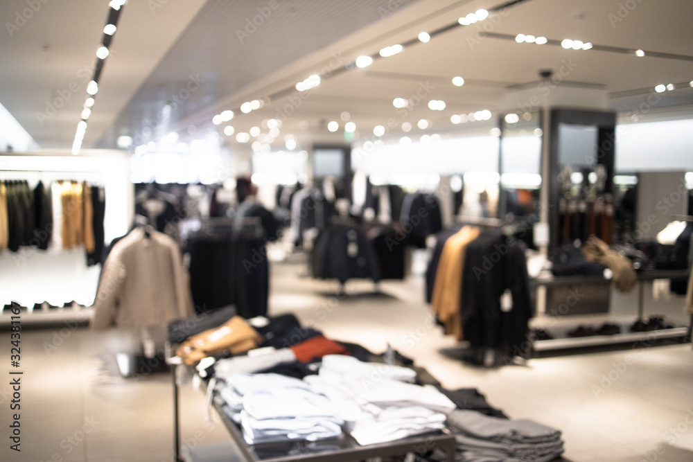 Fototapeta Fashionable clothing store in shopping center. Sale and seasonal change of collection. Led lighting on the ceiling. Fire system and air conditioning system in retail shop. Blurred.