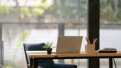 Close up view of workplace with open laptop, office supplies and decorations