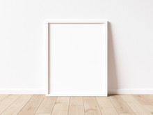 Vertical White Frame Mock Up On Wooden Floor With White Wall. 3D Illustrations.