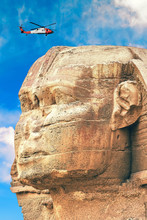 Red Helicopter Flies Over The Great Sphinx. Closeup