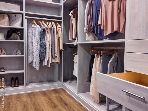 walk in closet with clothes hanging and shoes on shelving Fototapet