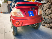 Closeup Image Of Dasbled Person Sign On The Electric Wheelchair With Three Wheels