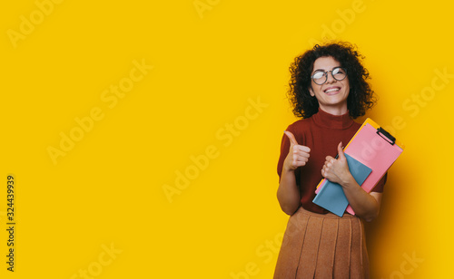 Photo Lovely curly haired student holding some books is recommending something by posi