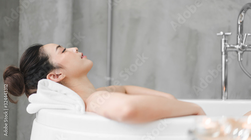 Slika na platnu Beautiful young asia woman enjoy relaxing taking a bath with bubble foam in bath