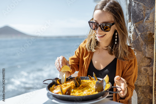 Fotografía Woman eating paella, traditional spanish dish, while sitting at the restaurant terrace near the ocean