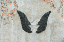 Dark Wings Decoration Hanging On Grungy Cement With Cracks Wall