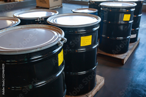 Photo Group of steel drums storing hazardous waste in a sheltered accumulation area