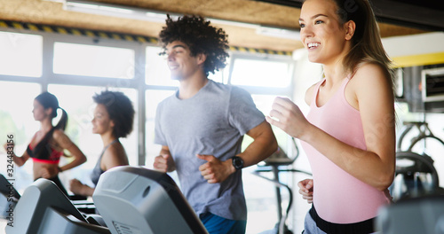 Leinwand Poster Group of people exercising in a gym cardio training and running