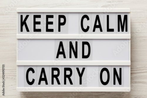 Fototapeta 'Keep calm and carry on' words on a lightbox on a white wooden background, top view. Overhead, from above, flat lay. obraz