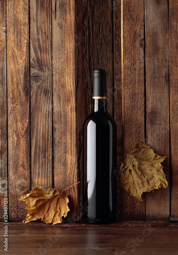 Cuadros en Lienzo Bottle of red wine and dried vine leaves on a old wooden background