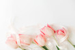 Pink tulips with ribbon and hearts on white background, flat lay. Stylish soft spring image. Happy womens day. Greeting card mockup with space for text. Happy Mothers day. Hello spring