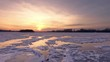 AERIAL: Flight over a frozen river during a blood-red sunset. Colorful landscape