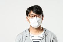 感染症予防の為に衛生マスクをしている眼鏡をかけた日本人男性のバストアップ正面