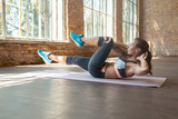 Sporty fit active young woman doing bicycle crunch situp exercise alone lying on mat wooden floor, strong sportswoman wear activewear training abs core muscles workout routine in sport gym studio