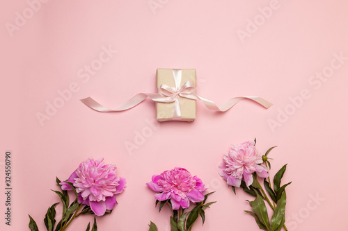 Romantic holiday composition with gift box with silk ribbon and pink peone. Mother's day concept