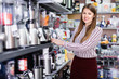 Young woman choosing blender in household appliances shop