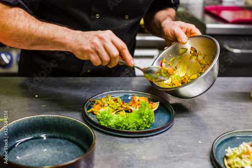 chef preparing food in restaurant at lunch time