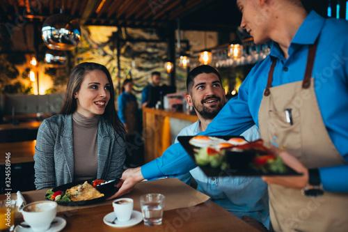 Fototapeta waiter serving food to customer in restaurant obraz