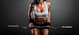Beautiful young fitness instructor woman posing in studio with weights. Close up detail