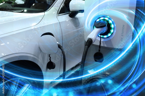 Cuadros en Lienzo EV Car or Electric vehicle at charging station with the power cable supply plugged in on blurred nature with blue energy power effect
