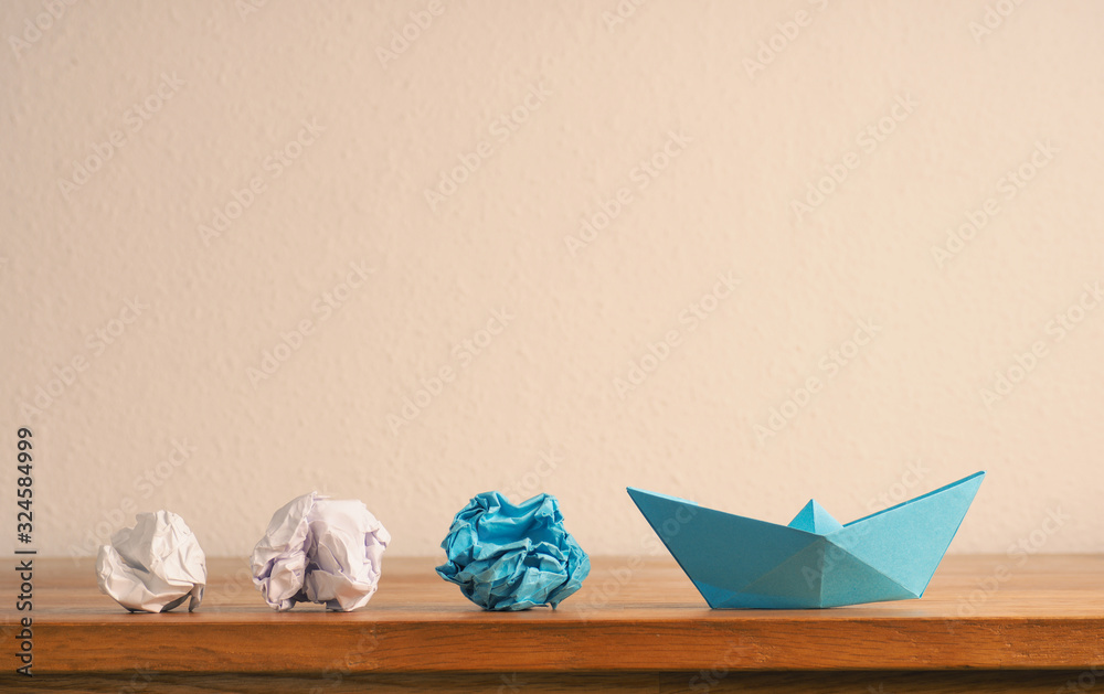 Fototapeta New ideas or teamwork concept with crumpled paper and paper boat