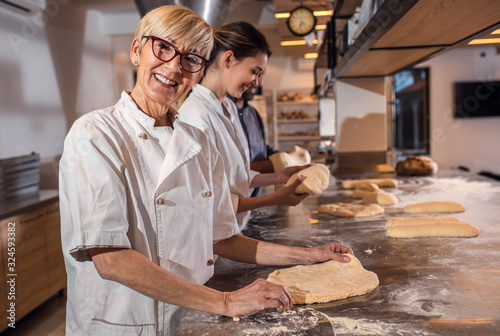 Fototapeta Portrait of senior female baker with coworkers in uniform preparing dough for baking bread in modern manufacturing