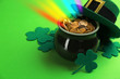 Leinwanddruck Bild - Pot with gold coins, hat and clover leaves on green background, space for text. St. Patrick's Day celebration