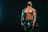 Man athlete bodybuilder. Muscular young fitness sports guy doing workout with dumbbell in fitness gym