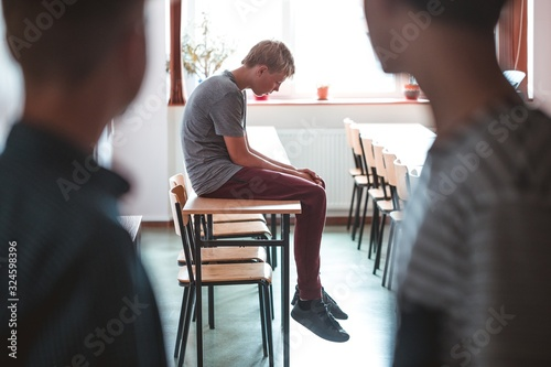 Fotografie, Obraz Sad teenage boy sitting alone at school, bullying among children concept