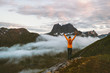 Woman raised hands over clouds in mountains sustainable travel vacations adventure healthy lifestyle outdoor eco tourism in Norway summer activity harmony with nature concept