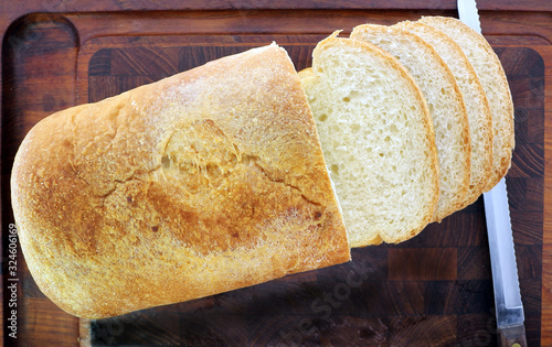 Overhead angle, Loaf of fresh home made bread, sliced, on dark cutting board,  with knife towards the side Wallpaper Mural