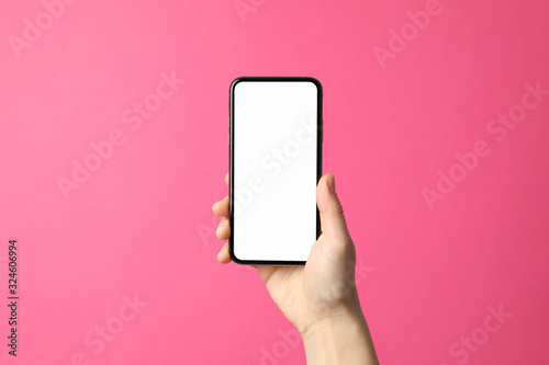 Female hand holds phone on pink background. Empty screen - 324606994